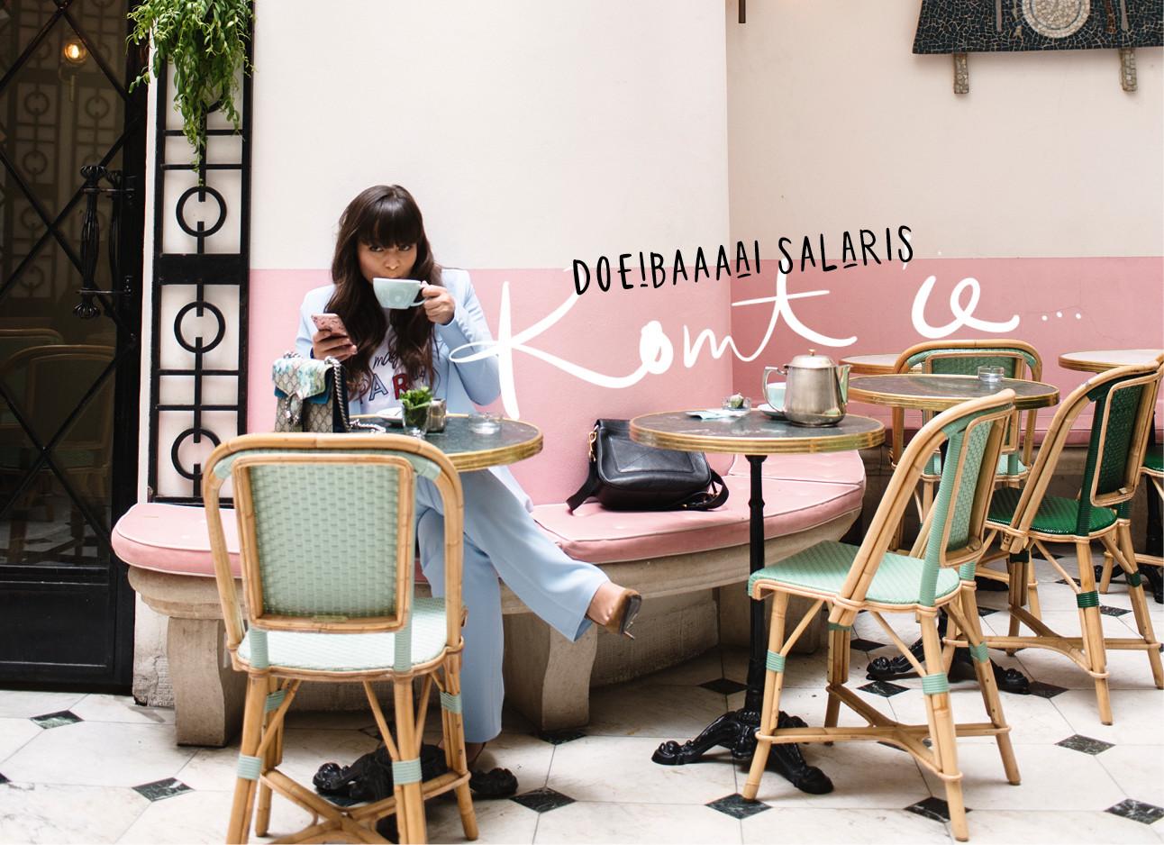 Kiki duren lachend op een terras met kop koffie in parijs een blauwe broek en jasje aan roze muren en groene stoelen