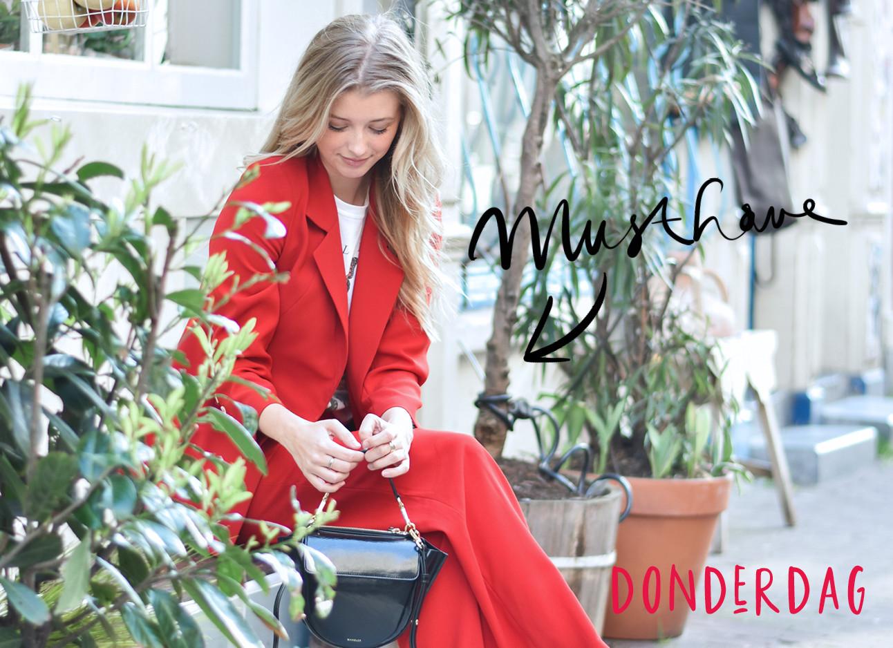 annabelle van hardeveld zit op een bankje tussen planten in een rood pak met een wit t-shirt en een zwarte hortensia wandler bag