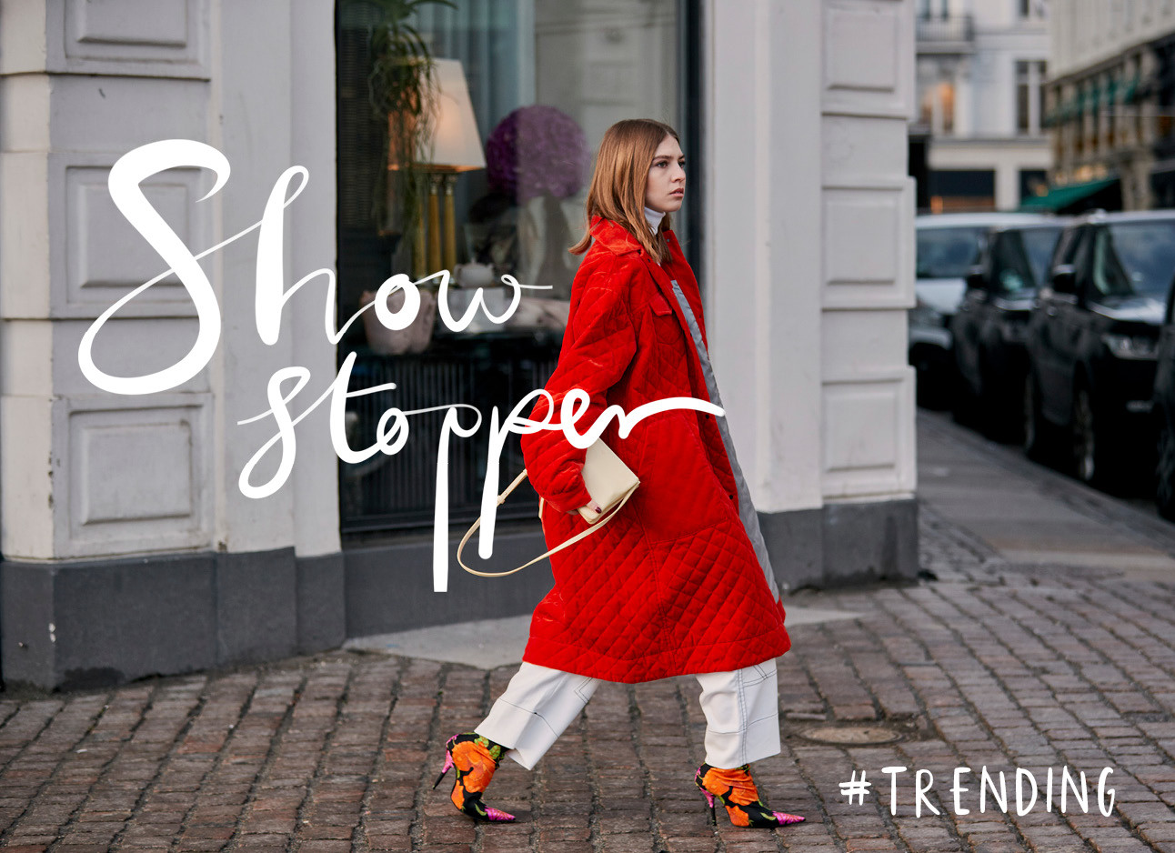 Vrouw in een rode jas lopend over straat