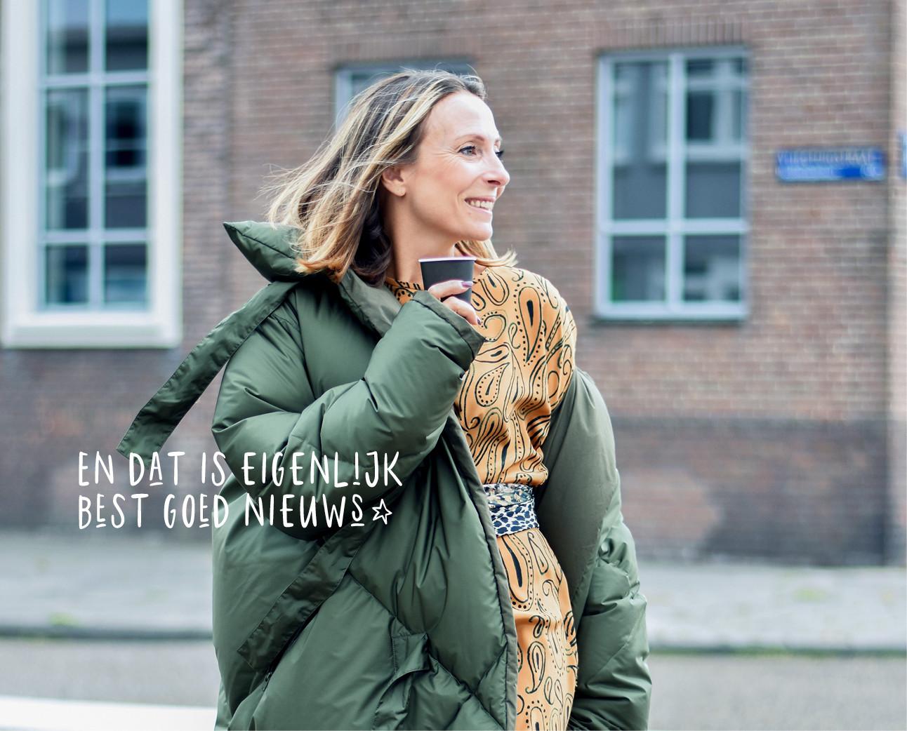 may-britt in de look of the day grote groene puffer jacket aan met een oker gelel jurk koffiie in haar handen