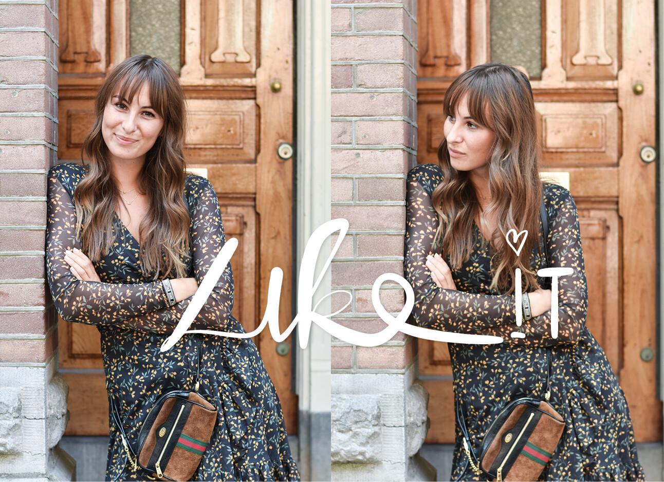 Lilian buiten bij een houten voordeur in een jurk met gucci tas