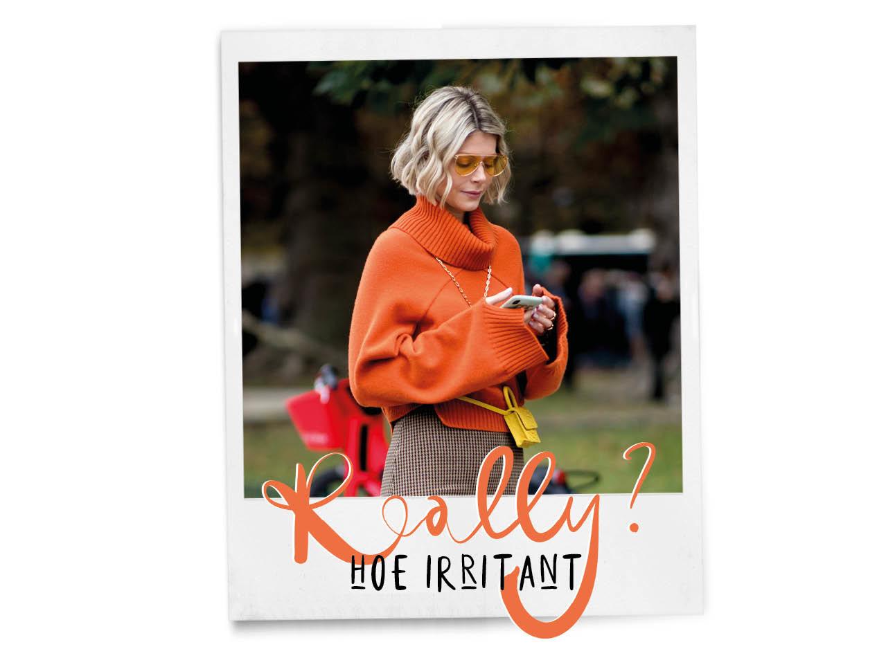 vrouw oranje trui aan kijkend naar haar telefoon