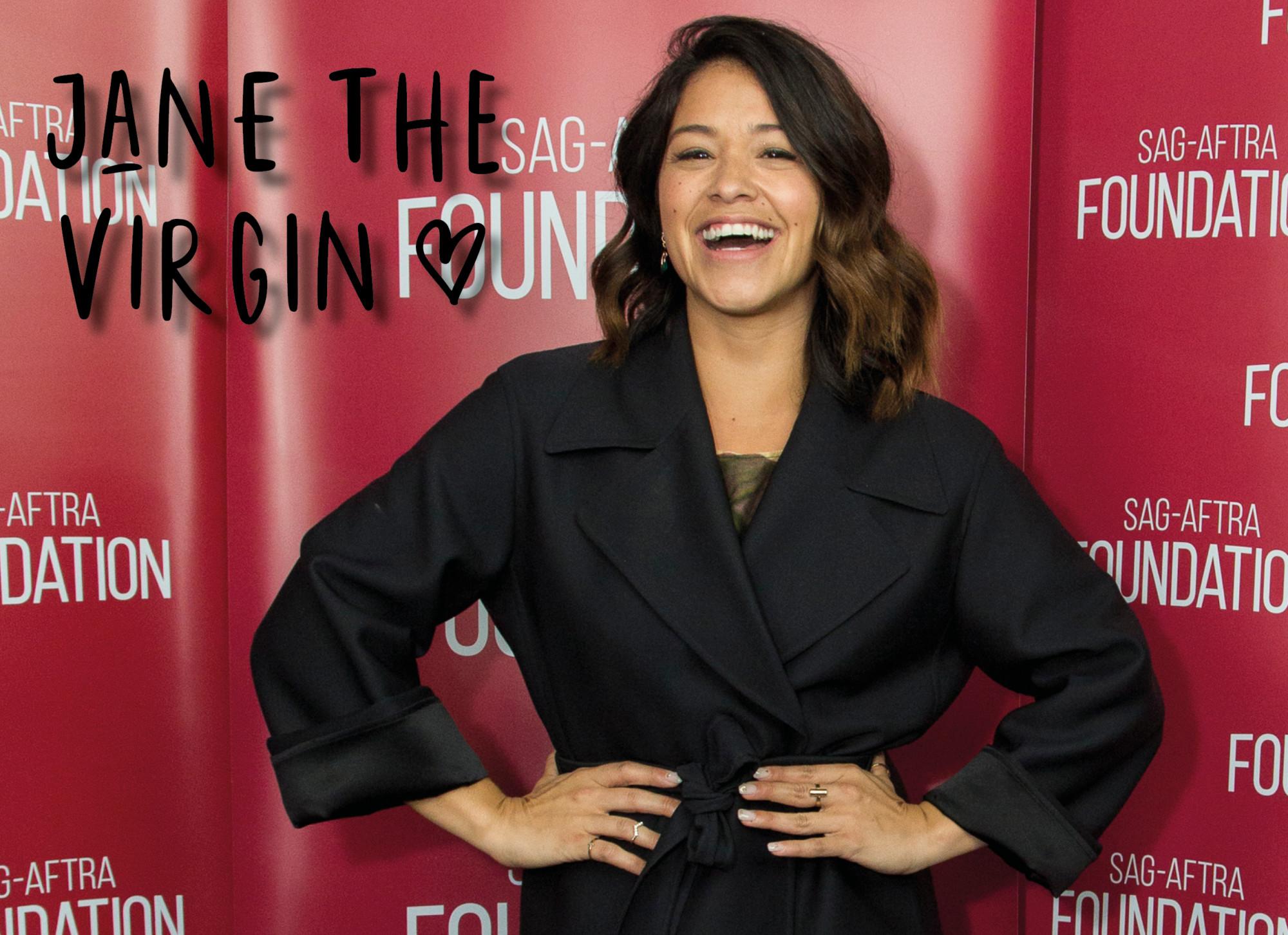 vrouw voor rode muur lachen met zwarte jas