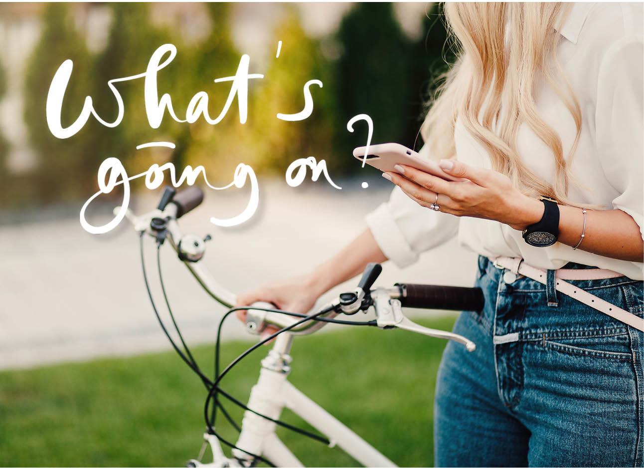blonde vrouw met een roze iphone in ene hand en een fiets in de andere hand, jeans, riem, blouse