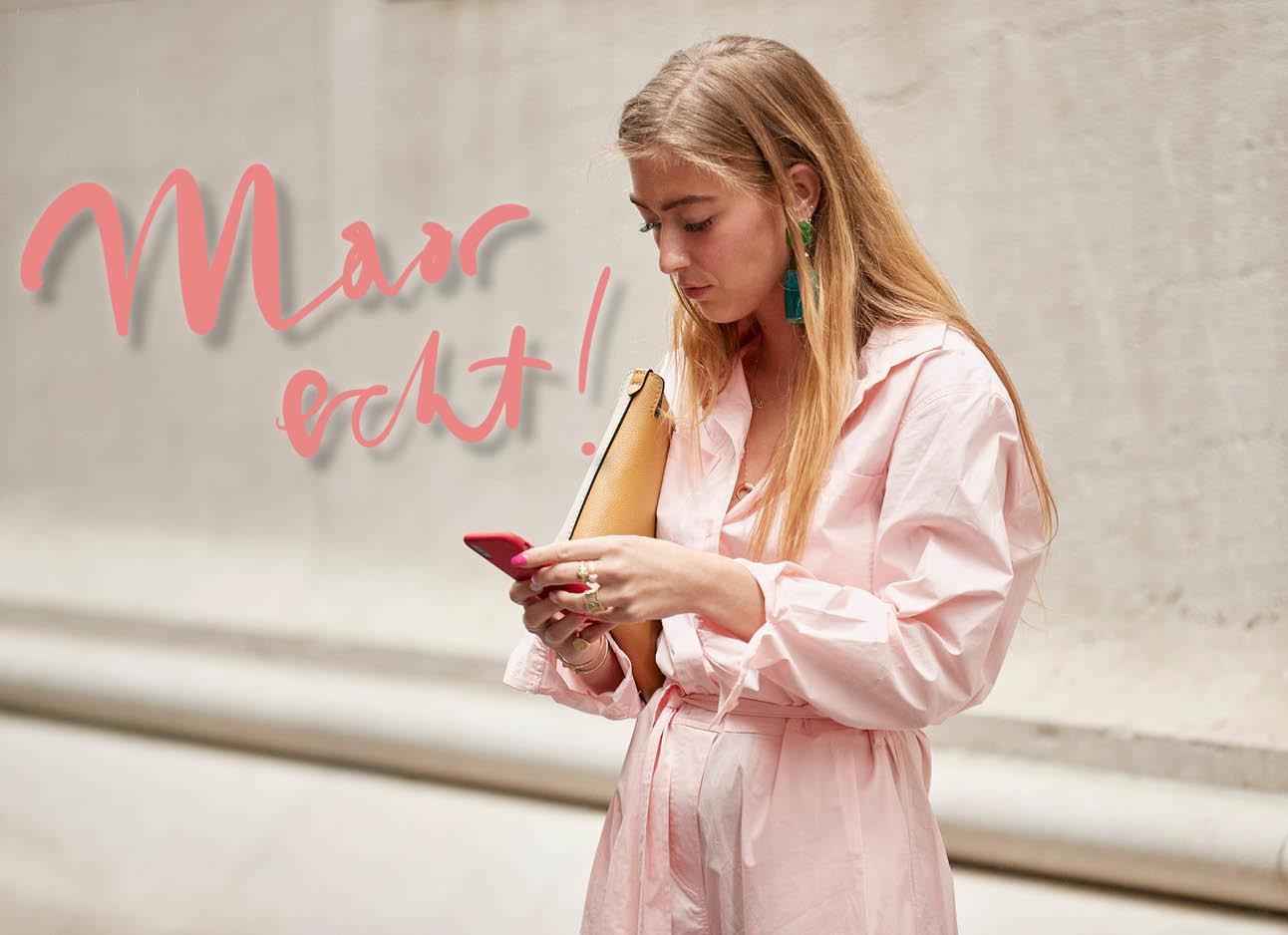 blonde vrouw in roze pak kijk op haar telefoon