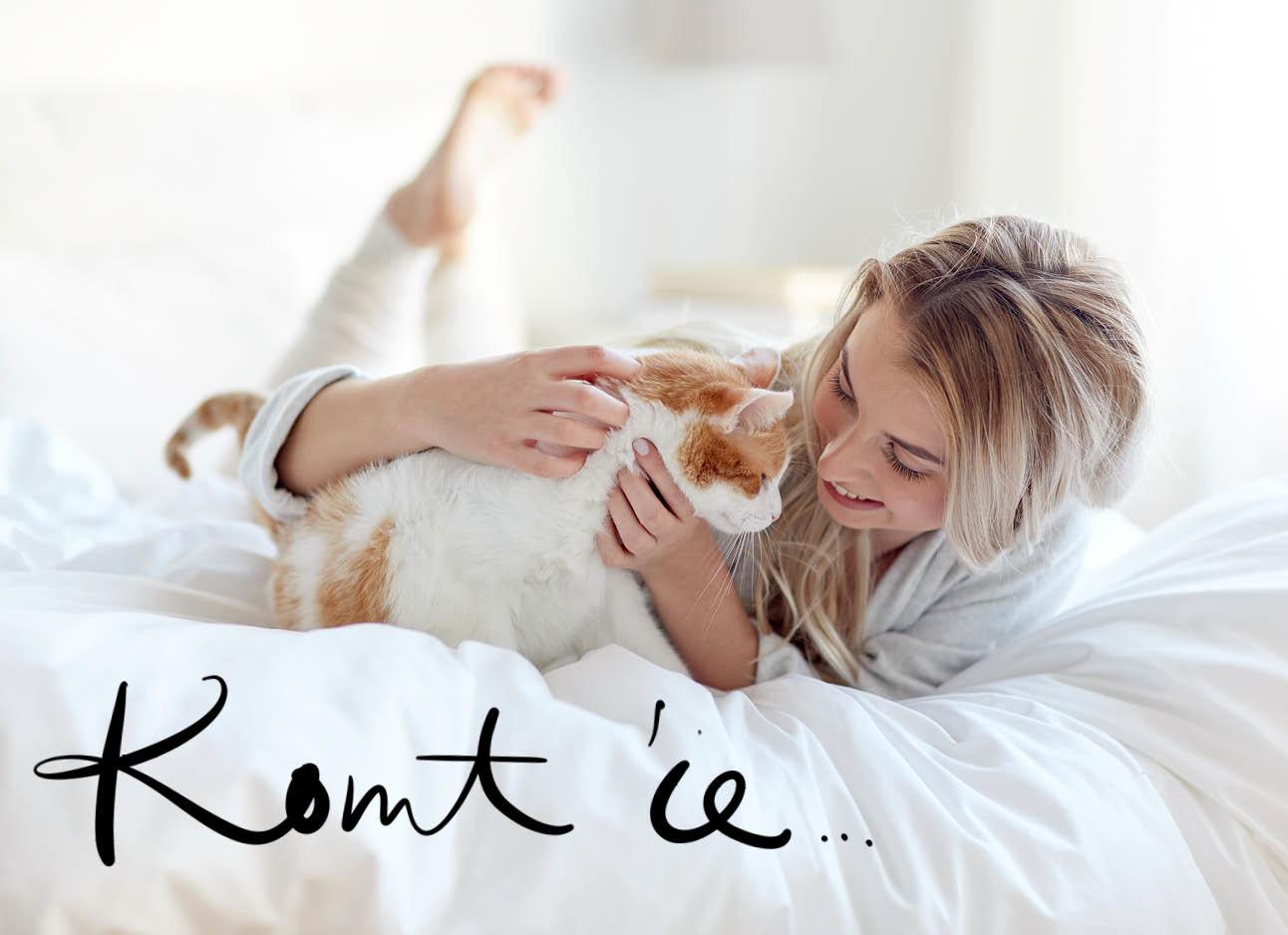 Vrouw en kat knuffelen op bed