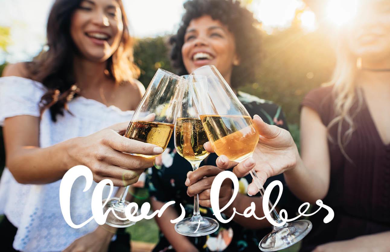 vrouwen wijn proosten gezellig lachen buiten