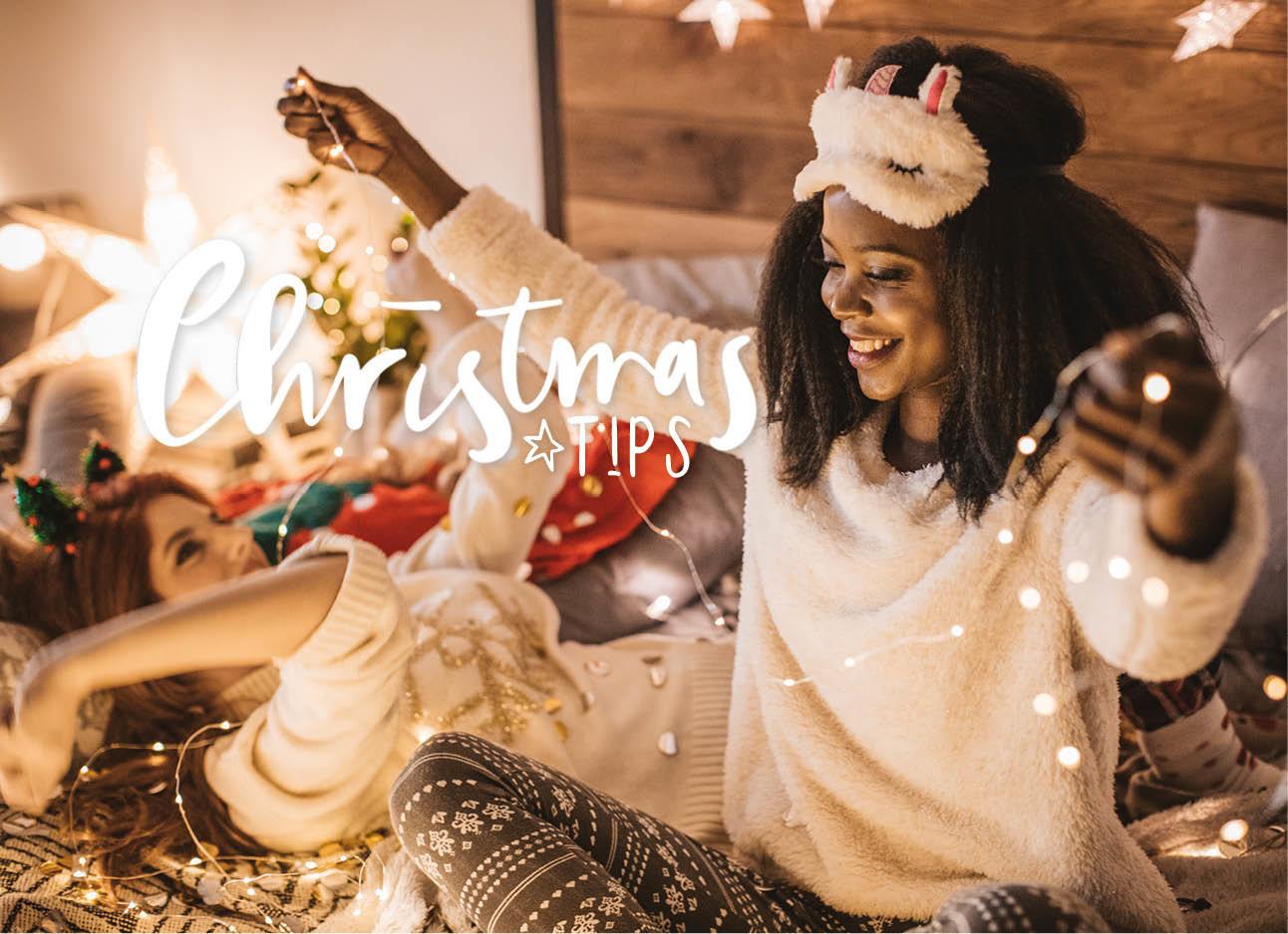twee vrouwen lachend op bed met kerstlichtjes in hun handen