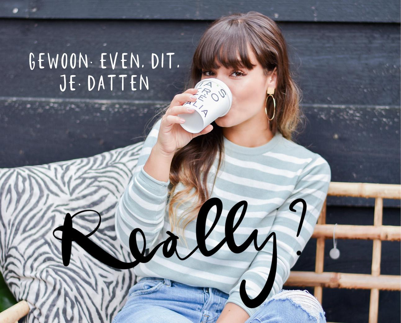 Kiki die koffie drinkt terwijl ze op een bank zit die van hout is gemaakt, ze draagt een mint groen getreept shirtje en een spijkerbroek