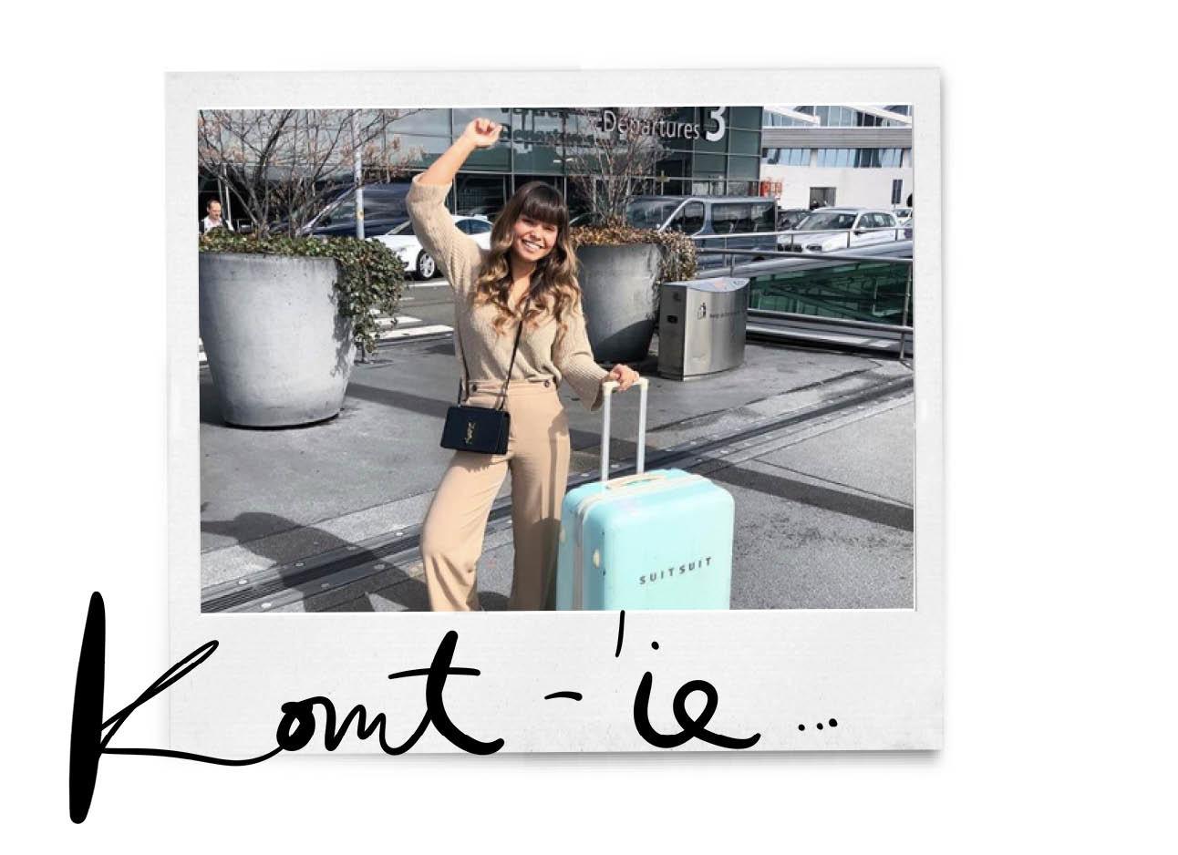 kiki in een beige outfit voor schiphol met een lichtblauwe suitsuit koffer