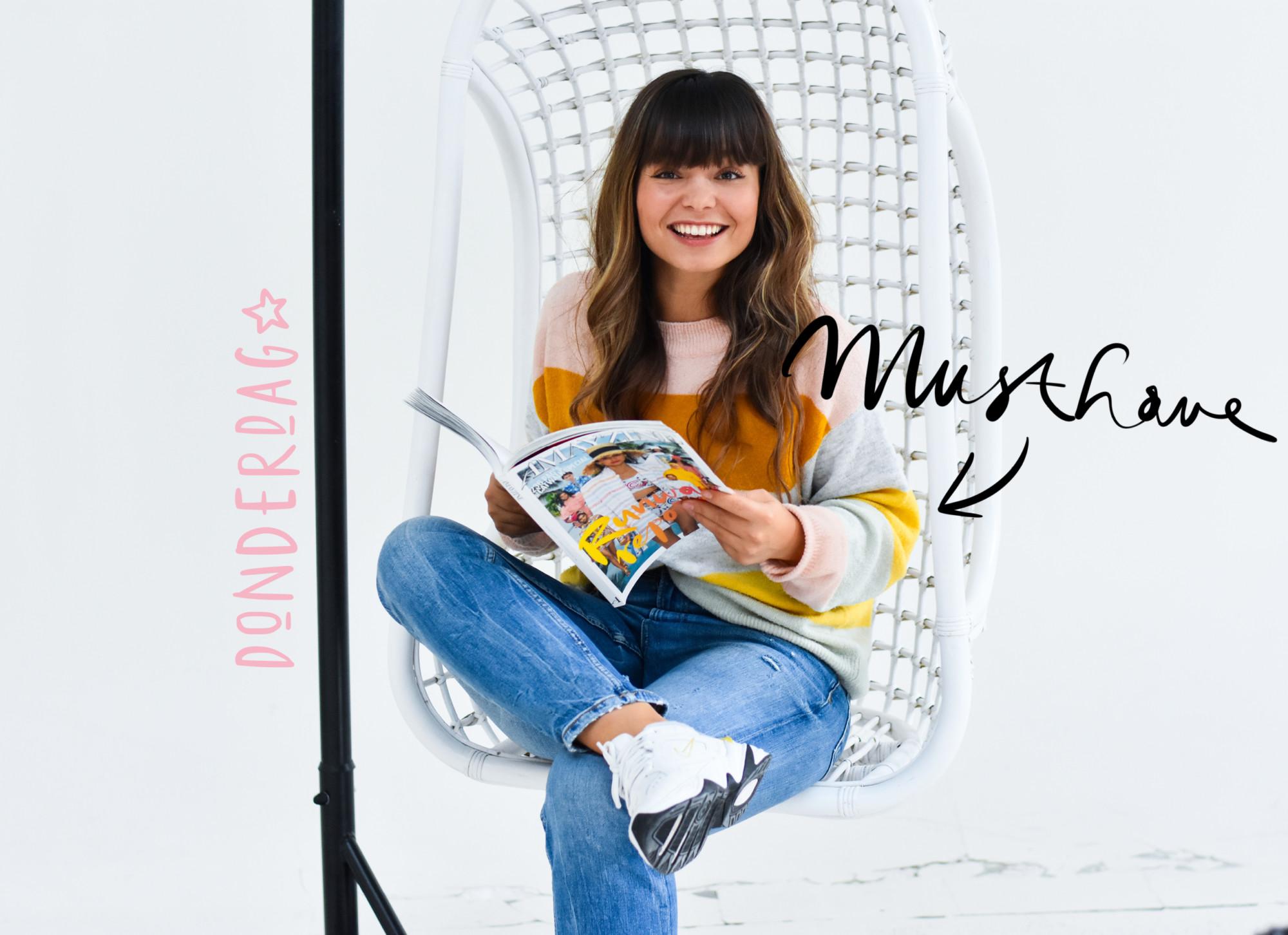 kiki duren in een stoel met witte achtergrond Ze draagt een gestreepte trui, blauwe jeans en witte sneakers van nike. In haar hand houd ze het magazine van amayzine vast. mustahave donderdag