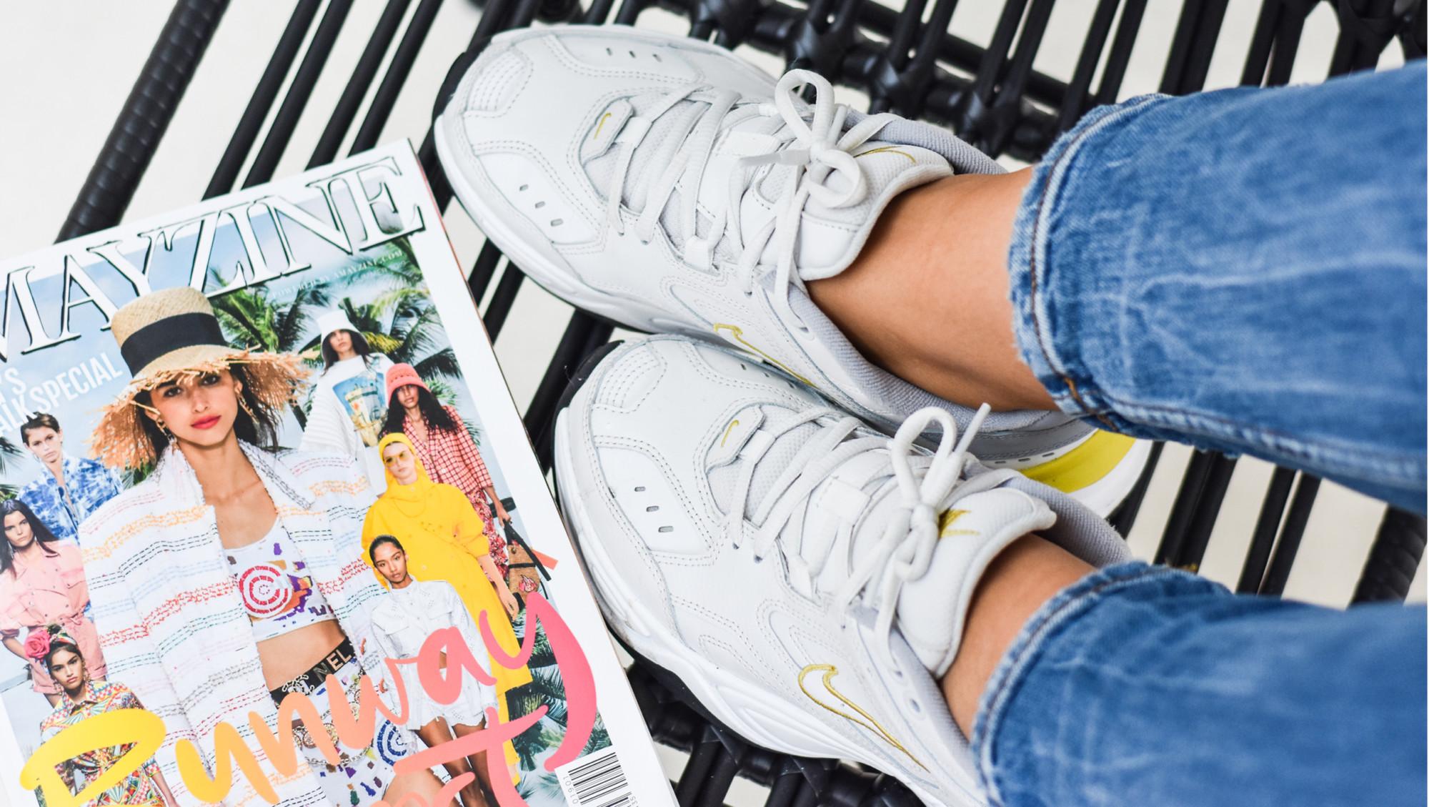 kiki draagt jeans en witte sneakers van nike met het magazine van amayzine