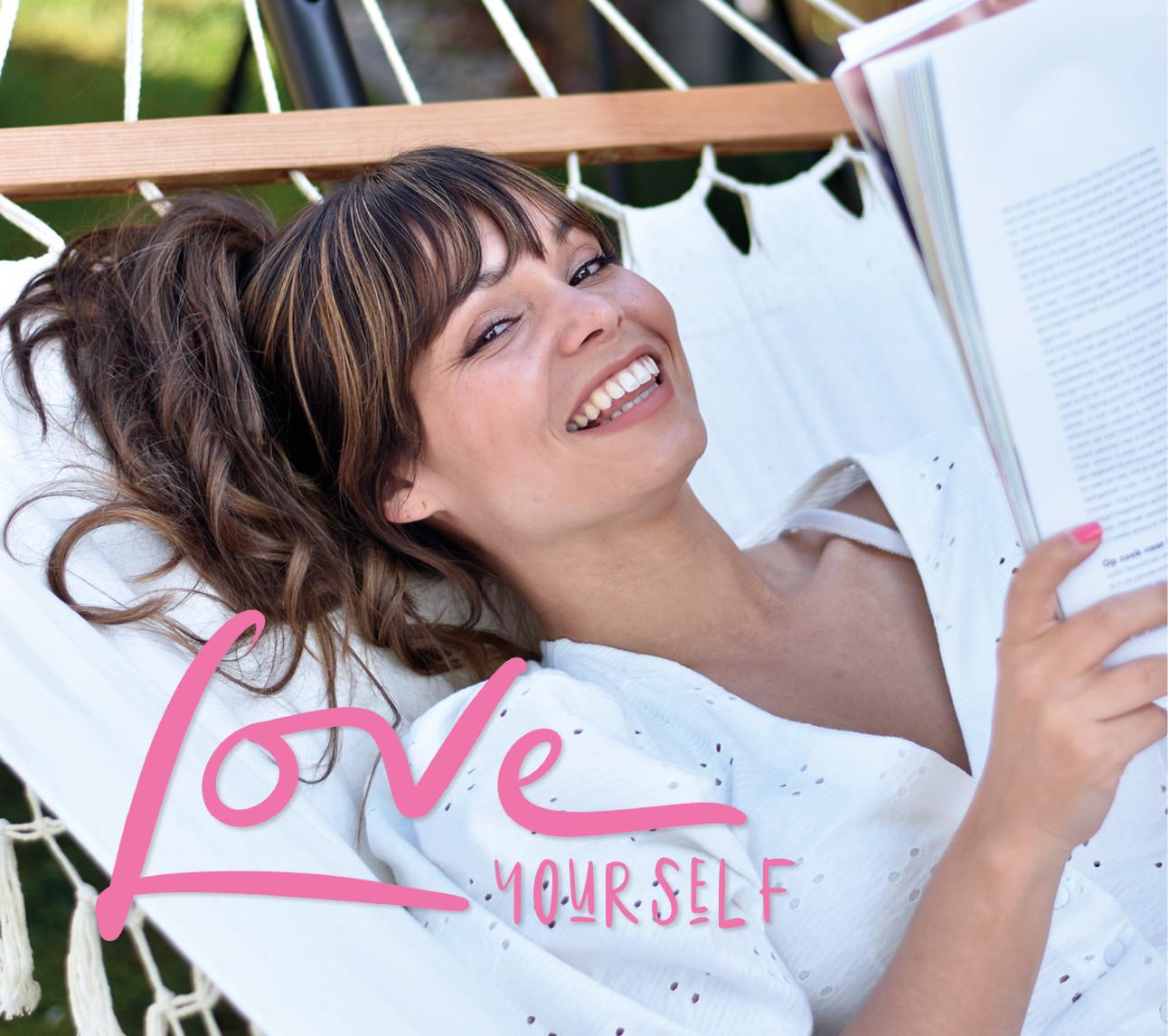 kiki lachend in een hangmat een tijdschrift aan het lezen