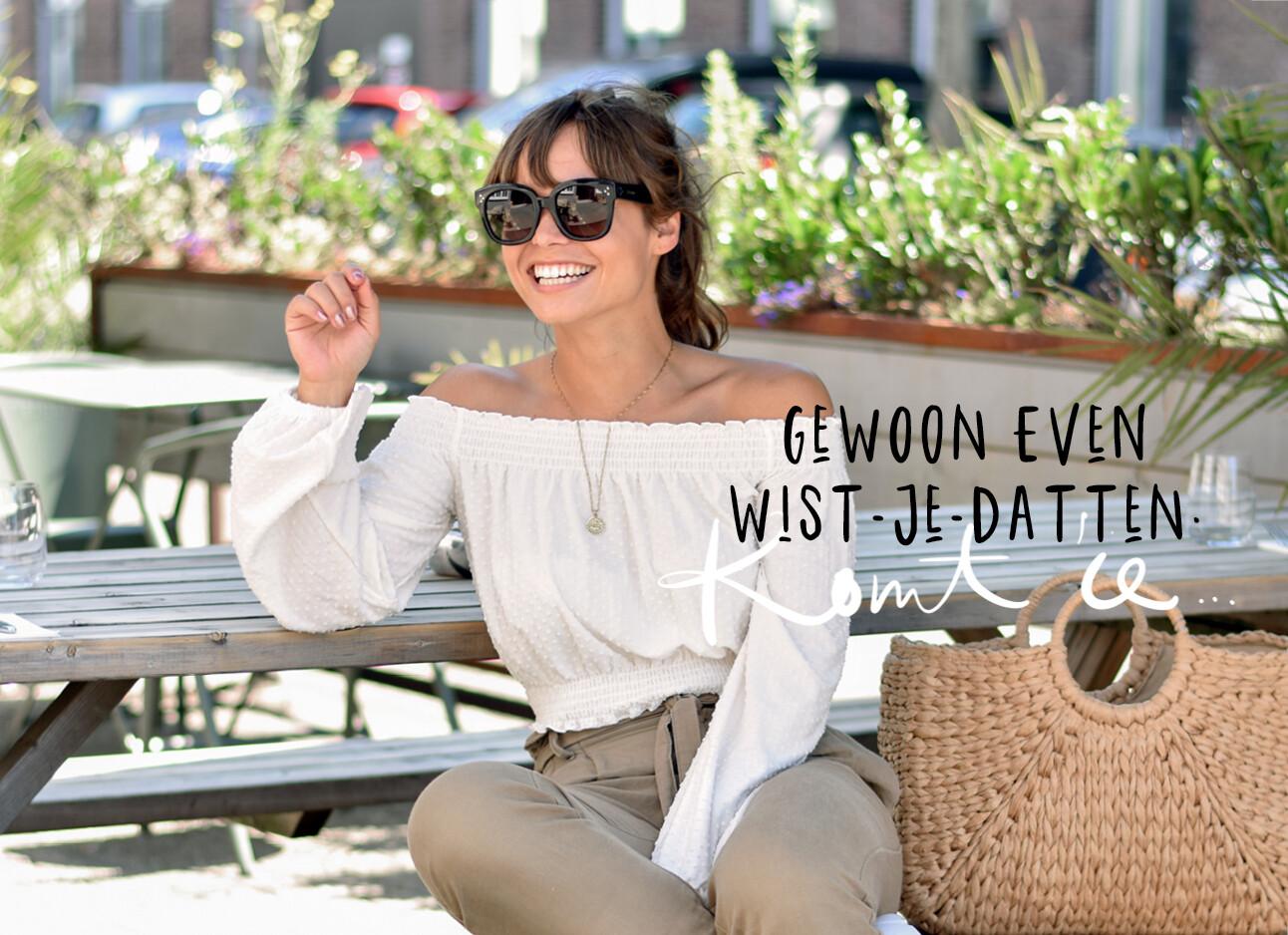 Kiki lachend zittend op een bankje met zonnebril