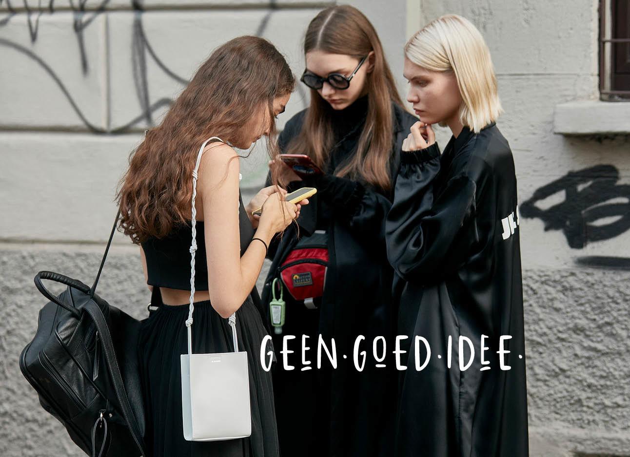 drie vrouwen staan op straat met zwarte kleding op hun telefoon te kijken