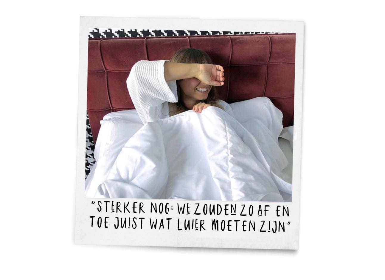 kiki duren in bed in een hotel met witte lakens en witte badjas, hand voor dr gezicht