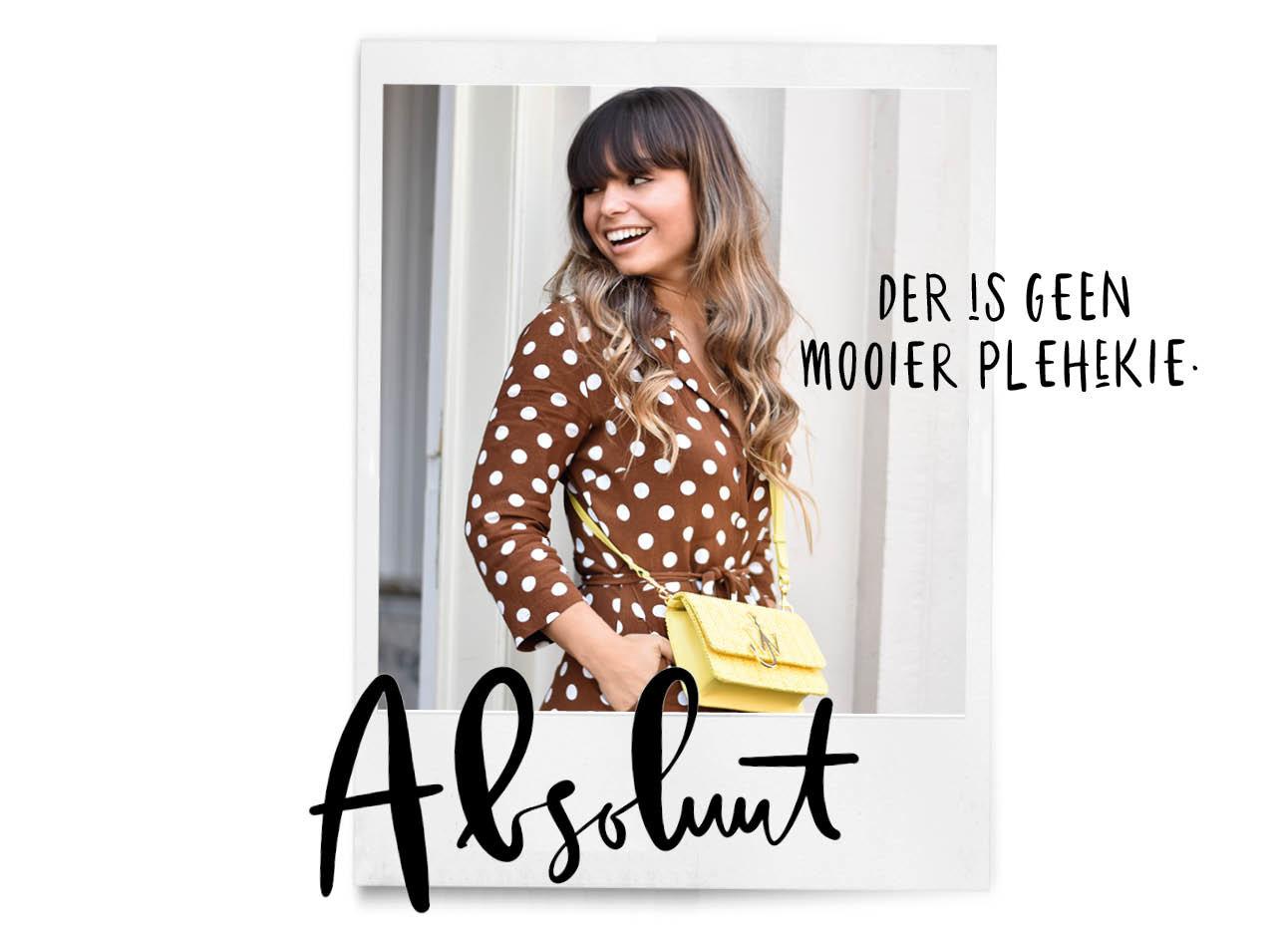 Kiki lachend met een gele tas en bruin pak met stippen