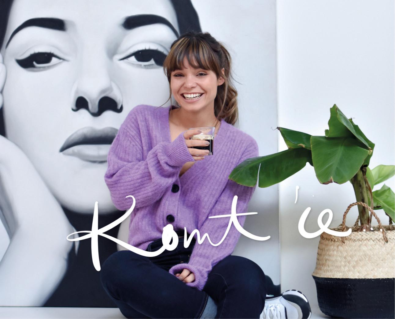 Kiki lachend in een paars vestje met een kop koffie