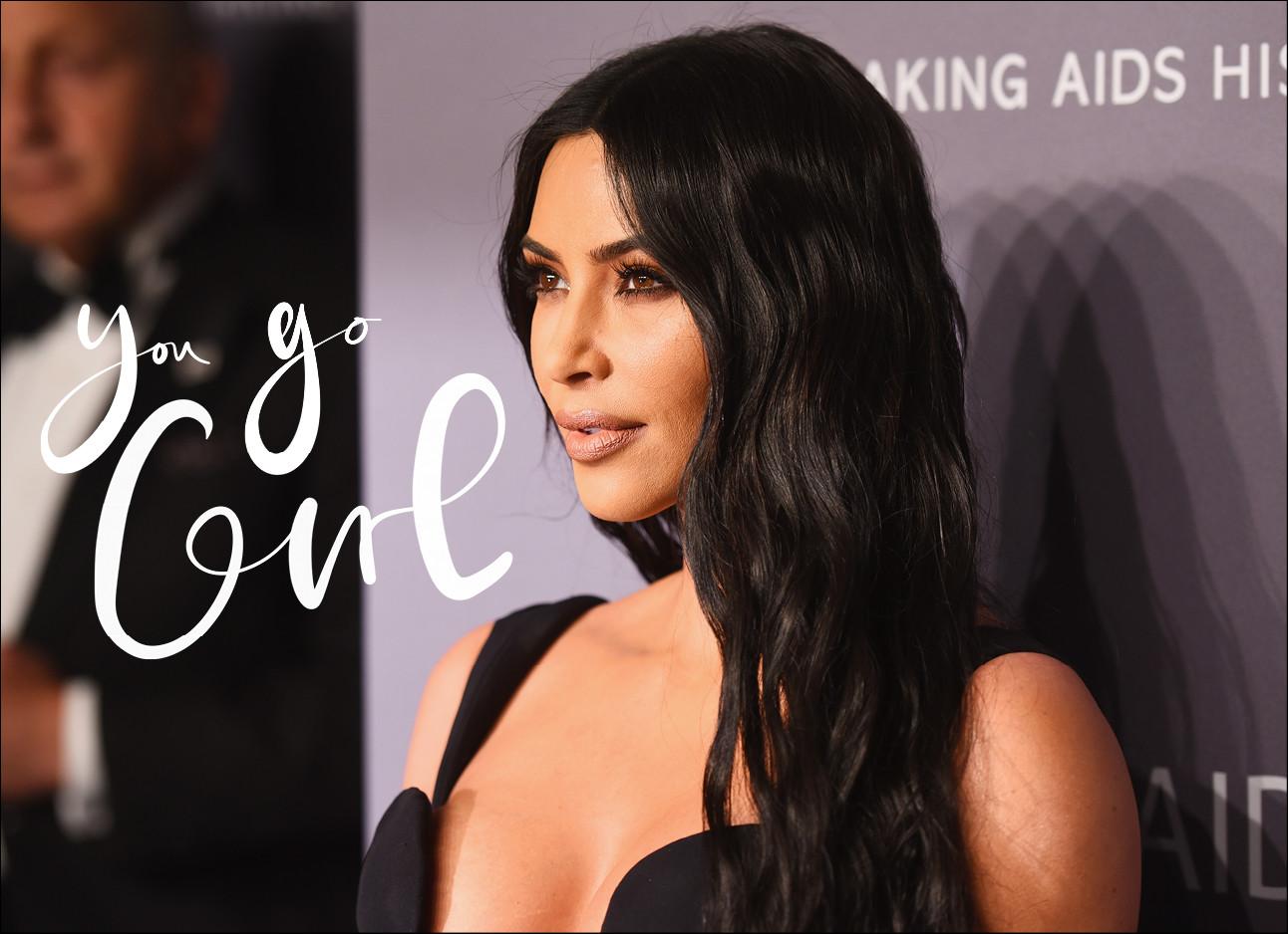 Kim Kardashian die in een zwarte jurk voor een paarse muur staat