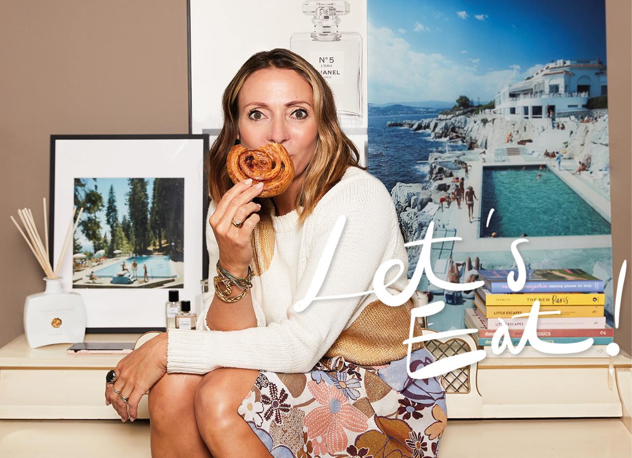 Vrouw zit op een bureau met een koekje