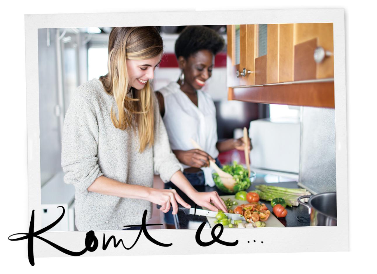 twee vrouwen in de keuken eten aan het snijden en lachen