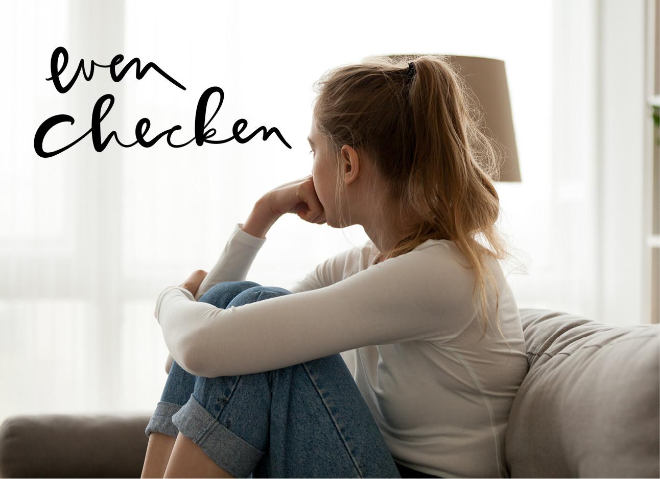 eenmeisje dat op de bank zit en naar buiten kijkt ze draagt een spijkerbroek en een witte col