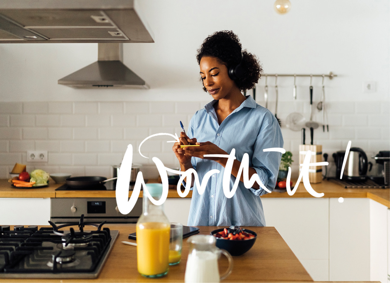 vrouw in de keuken met koptelefoon maakt een lijstje