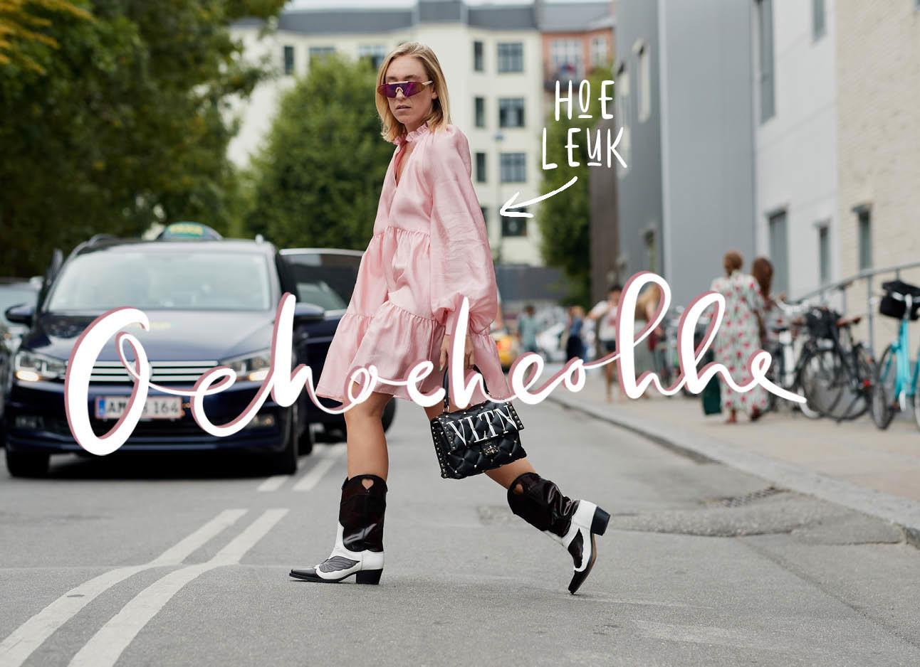 Meisje dat de straat oversteekt, ze draagt zwart met witte cowboy boots. ze draagt een roze tent jurk en achter haar lopen mensen en staan auto's
