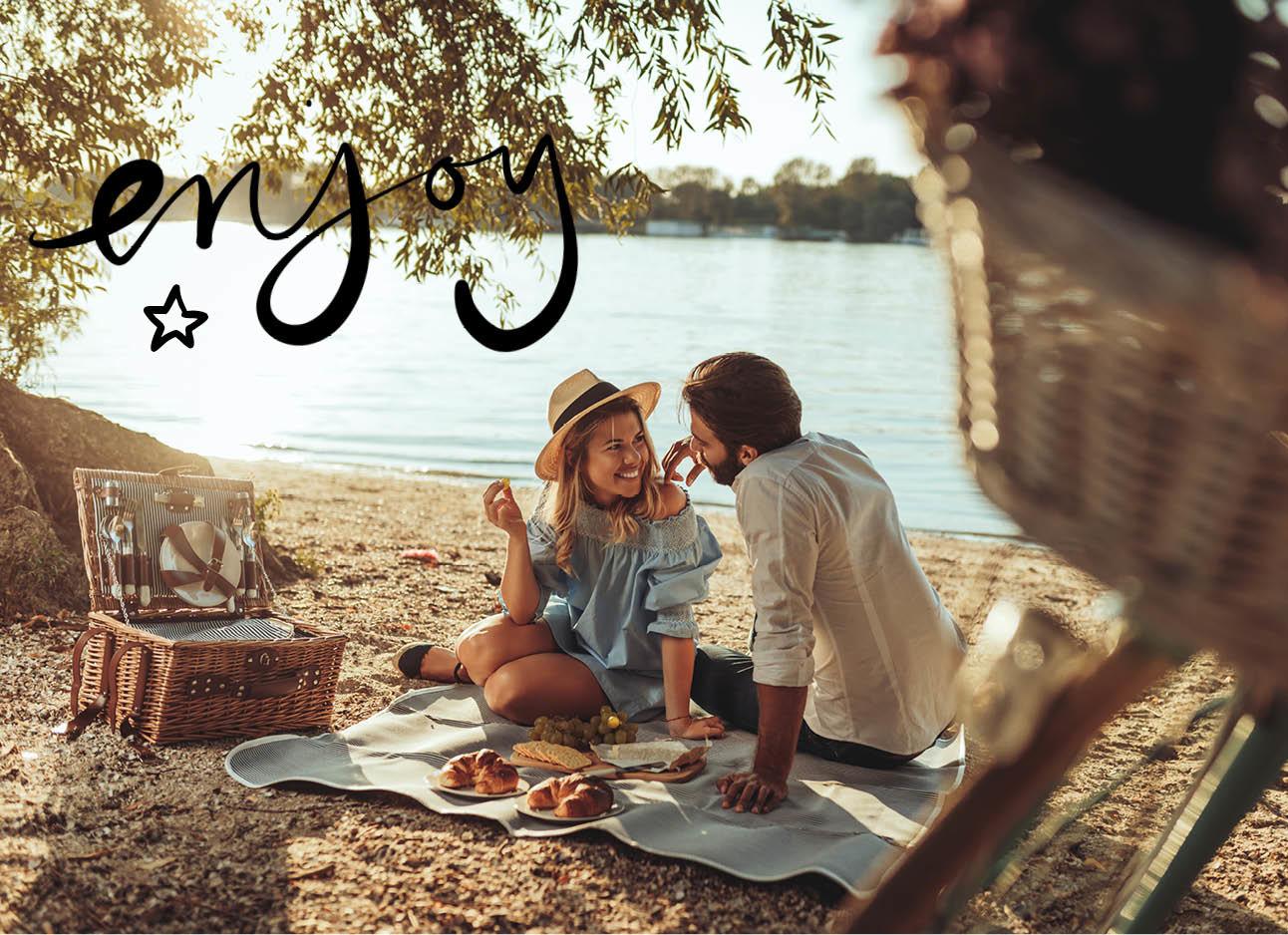Man en vrouw zijn buiten aan het water aan het picknicken, romantisch