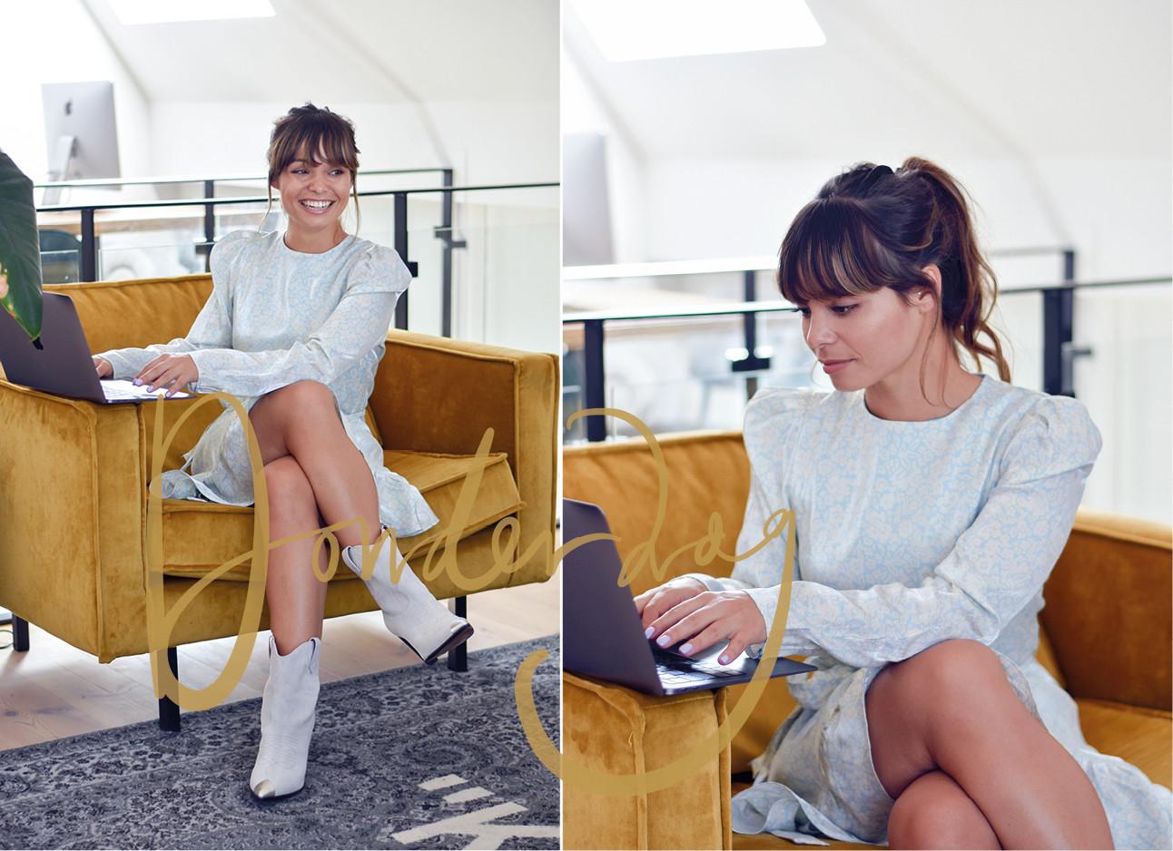 Kiki duren lachend met een jurkje aan achter haar laptop