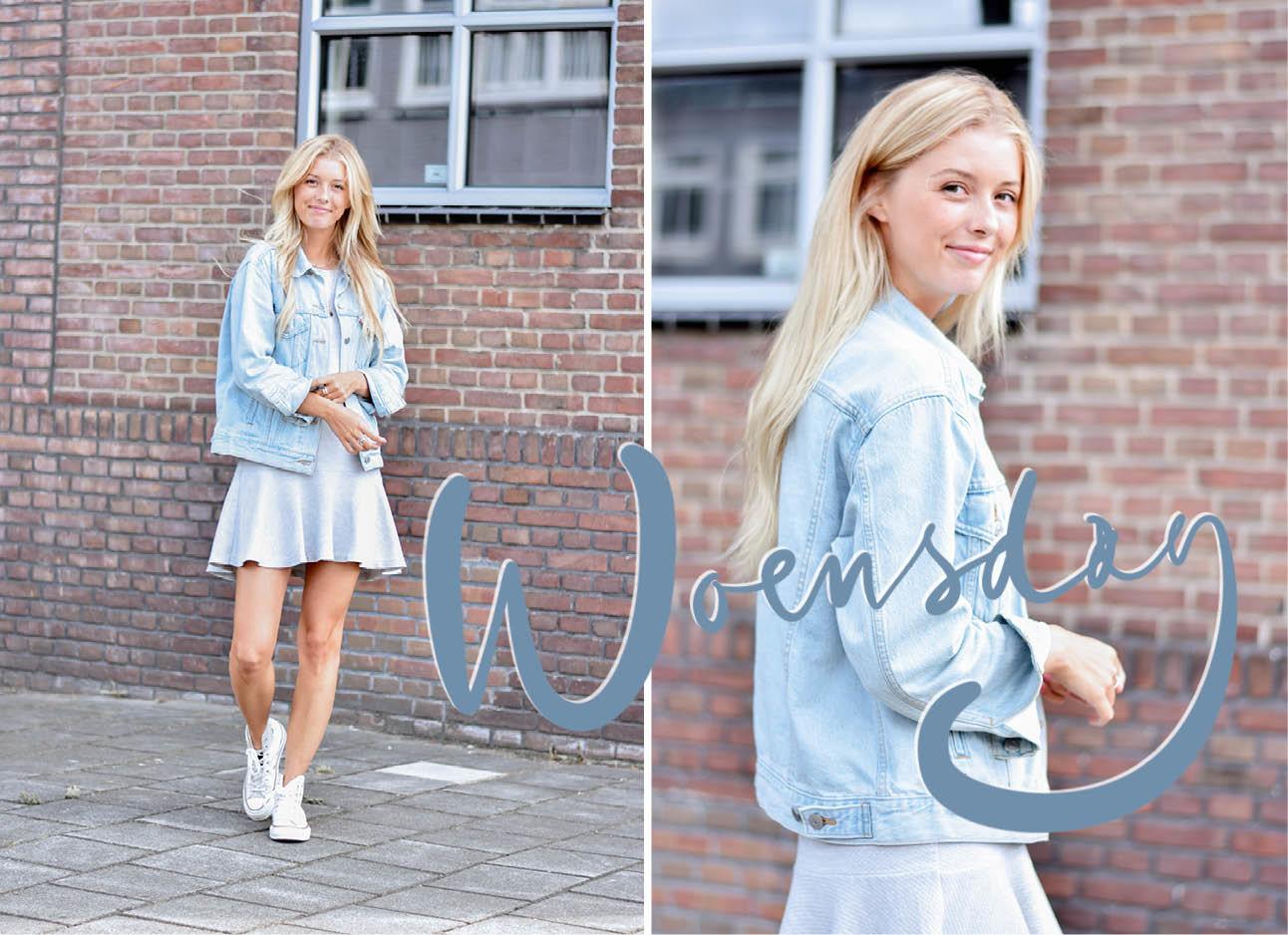 Meisje met spijkerjasje aan en een grijs jurkje. Voor een bakstenen muur met 1 groot raam. Ze draagt witte converse sneakers