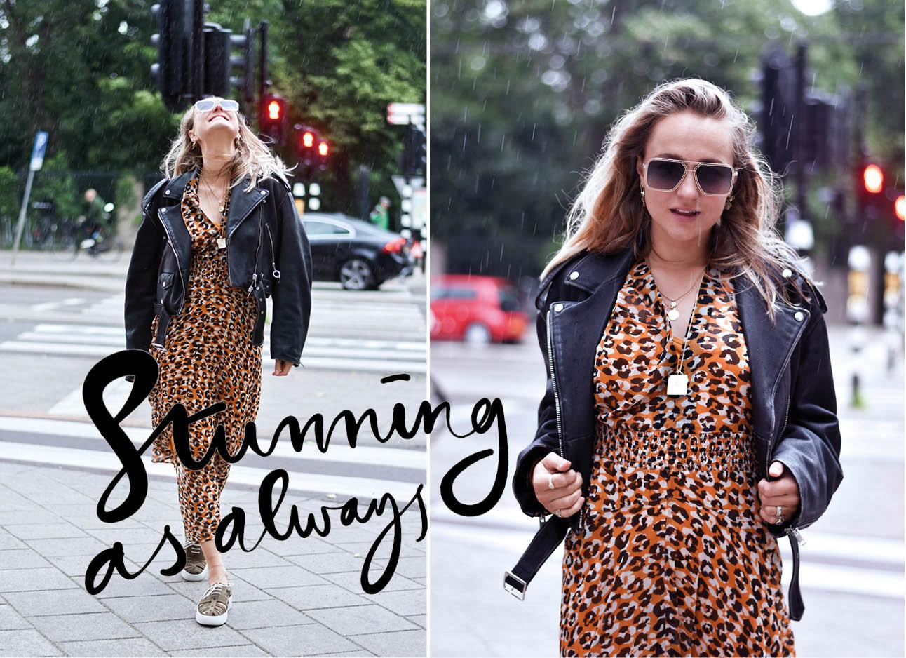 Carolien Spoor in de regen met een zonnebril op en leer jasje aan lange jurk in het park