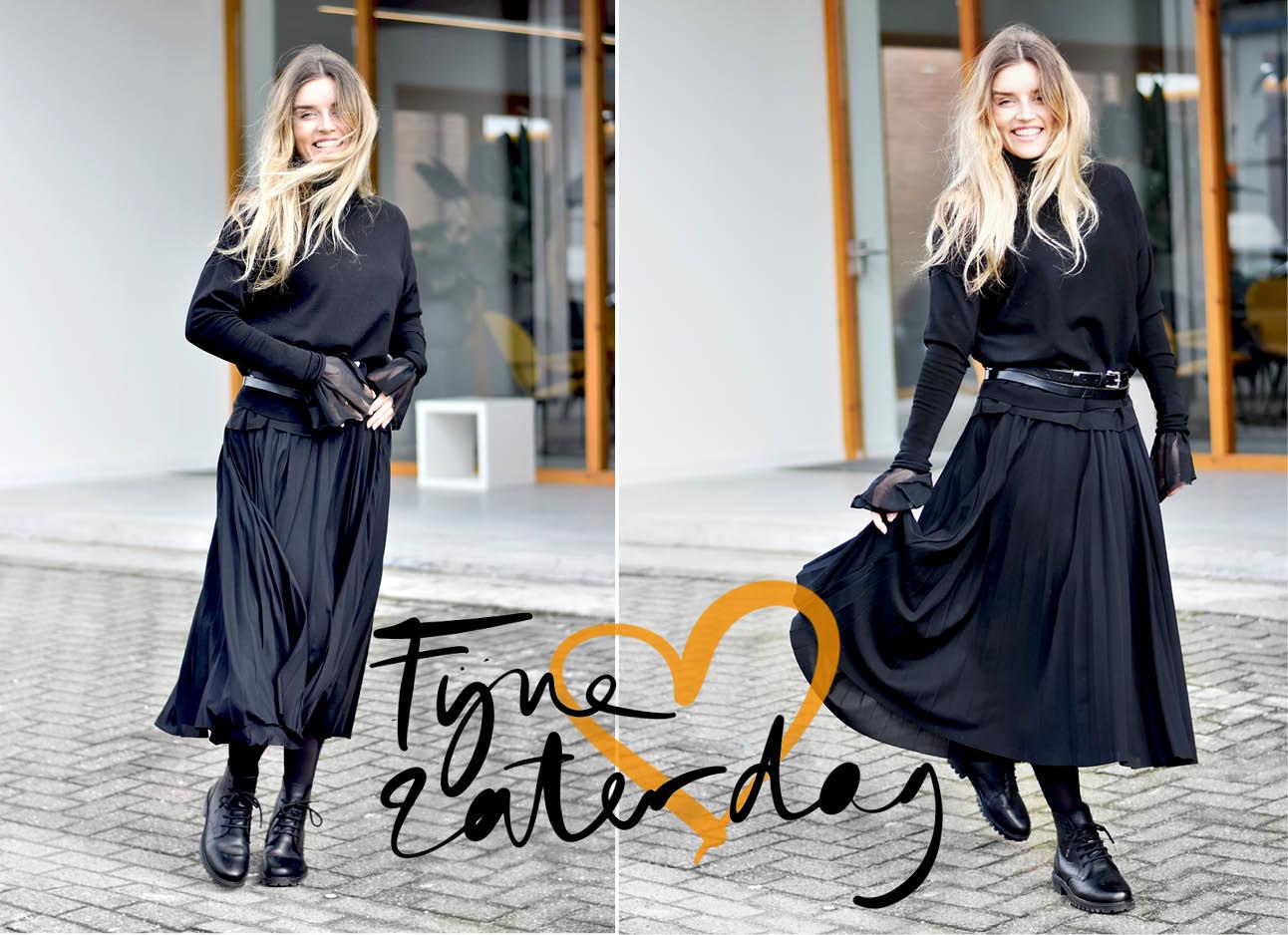 lotte in een zwarte rok, zwarte trui, zwarte top en leren boots