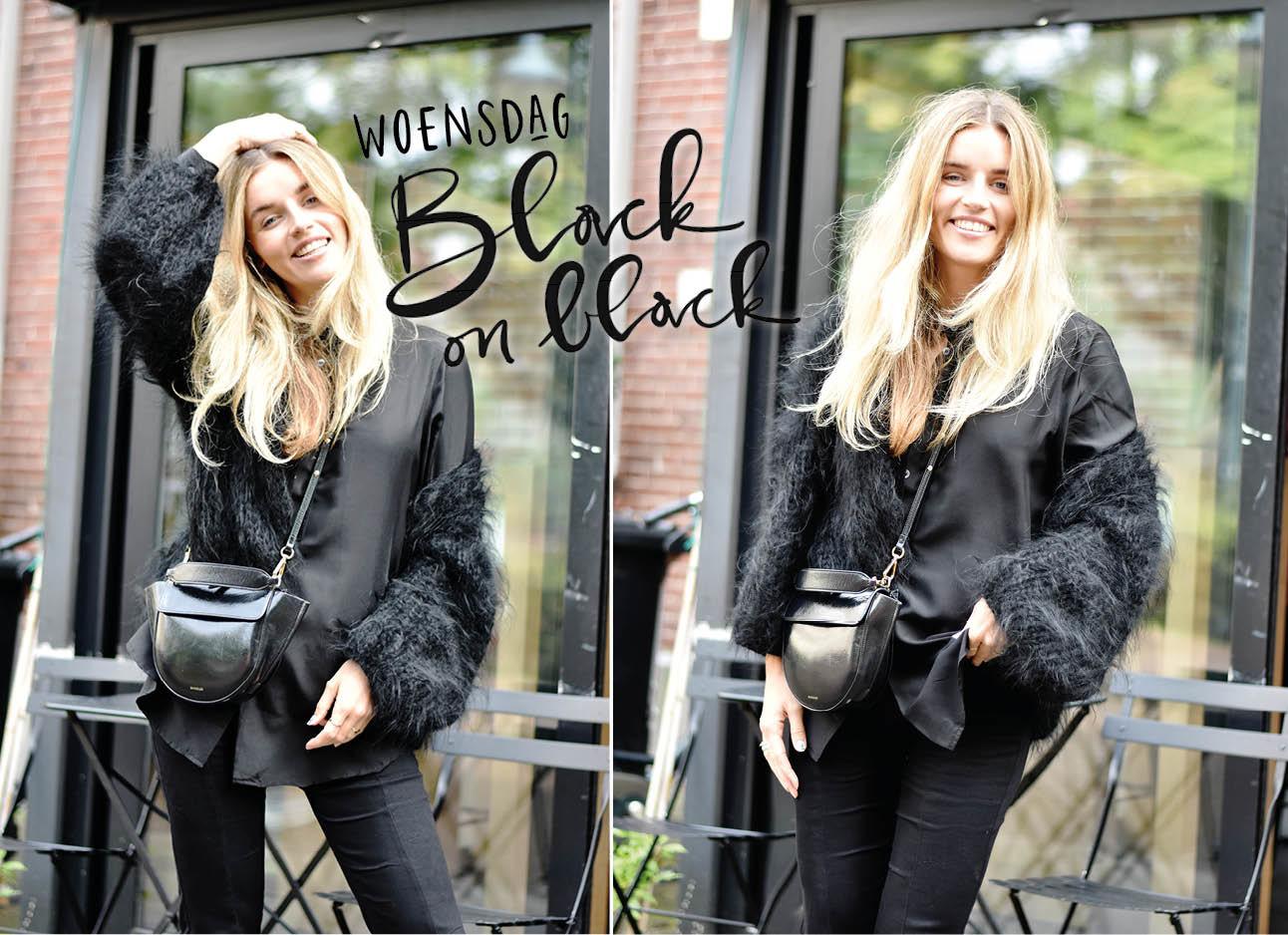 Lotte die een all-black outfit draagt terwijl ze staat voor een stenen gebouw met een groot raam