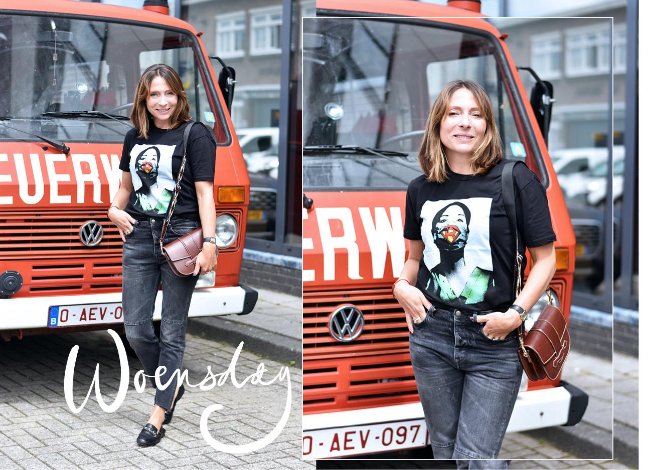 May-britt Mobach lachend in een jeans en tshirt met een bruine tas voor een brandweer auto