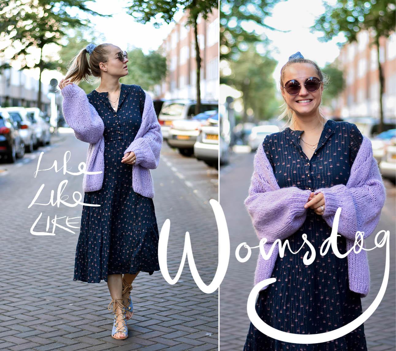 Carolien spoor lachend met zonnebril en jurk met vest aan op straat