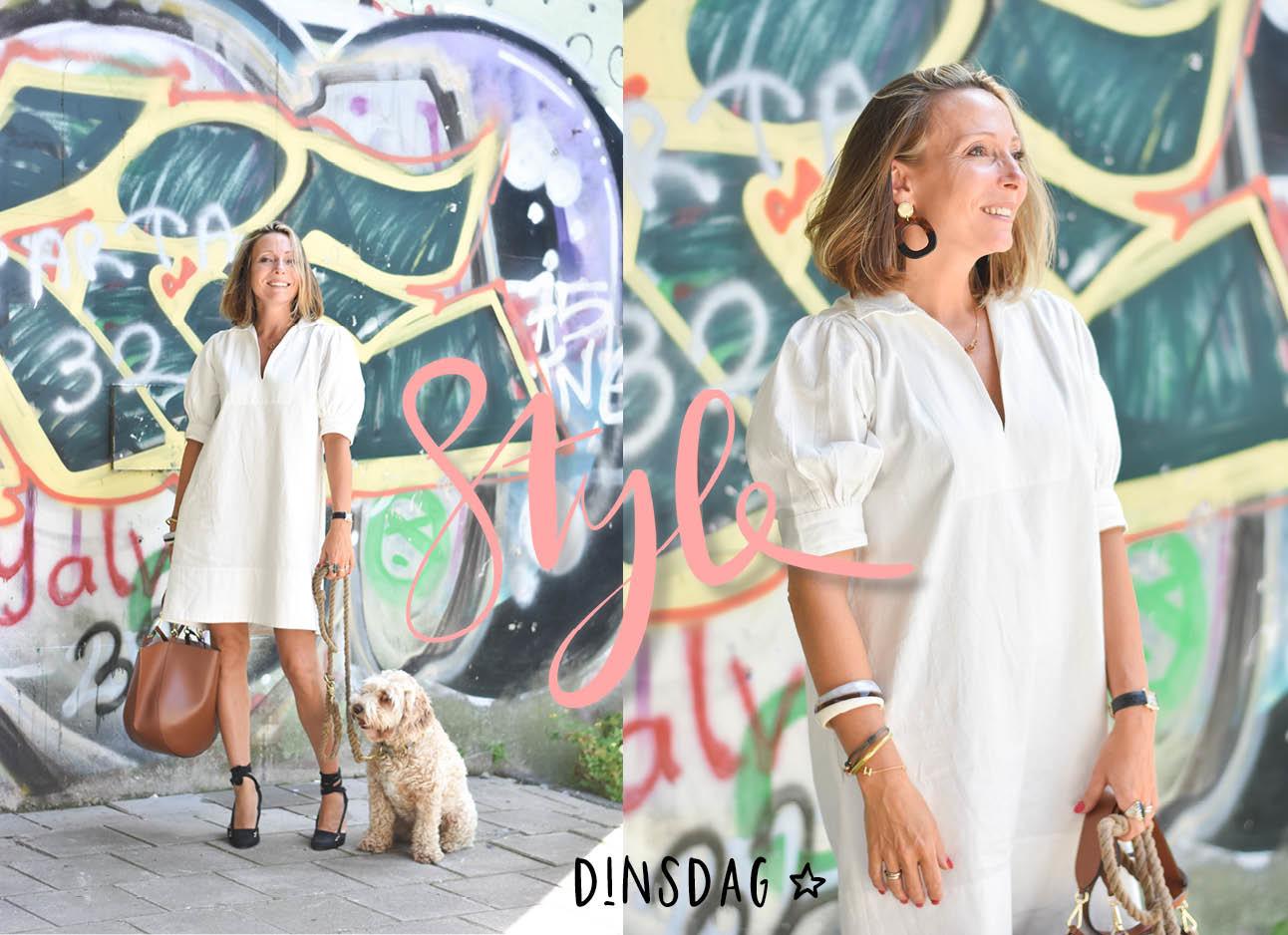 May-Britt in de look of the day in een witte jurk met een bruine hortensia wandlertas, zwarte espadrilles en monti aan de lijn