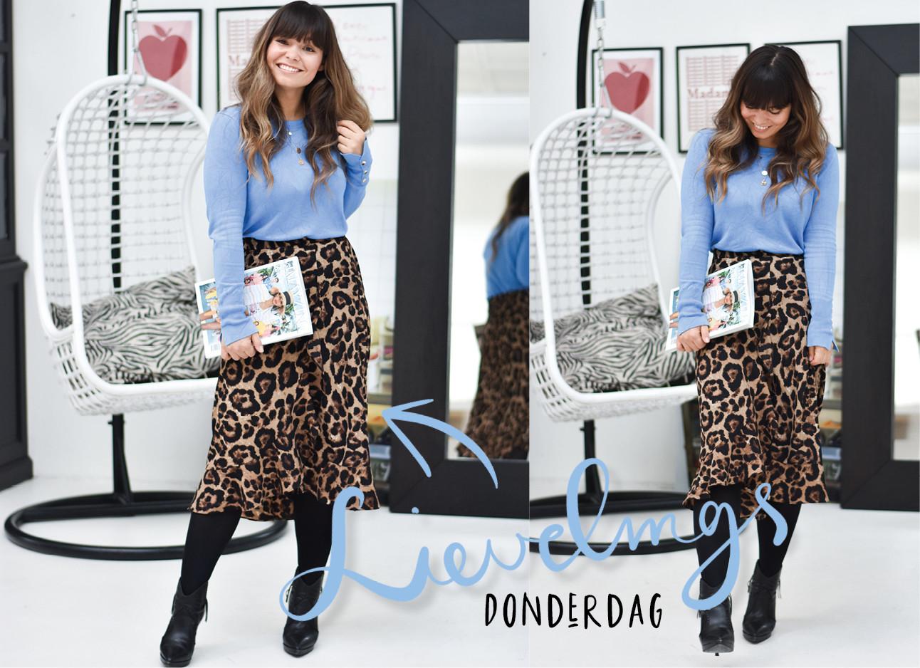 Look of the day kiki duren, ze draagt een midi panter rok met een lichtblauwe top en daaronder zwarte laarsjes. In haar hand heeft ze het amayzine runway report