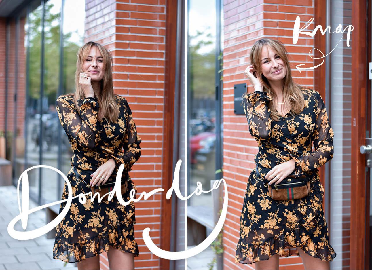 Een meisje draagt een bloemenjurkje. ze staat voor een bakstenen muur met een groot raam. ze draagt een heuptasje van gucci, het tasje is bruin