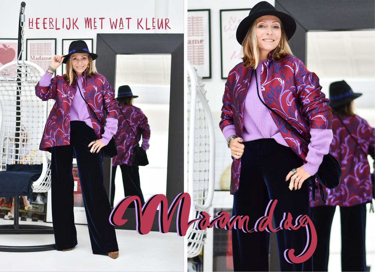 lofd may, paarse trui en jas. Met een hoed op, satijne broek en staat voor de spiegel