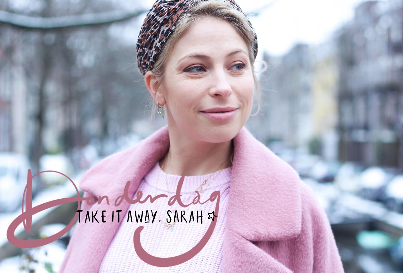 Sarah Chronis in roze jas op straat in Amsterdam