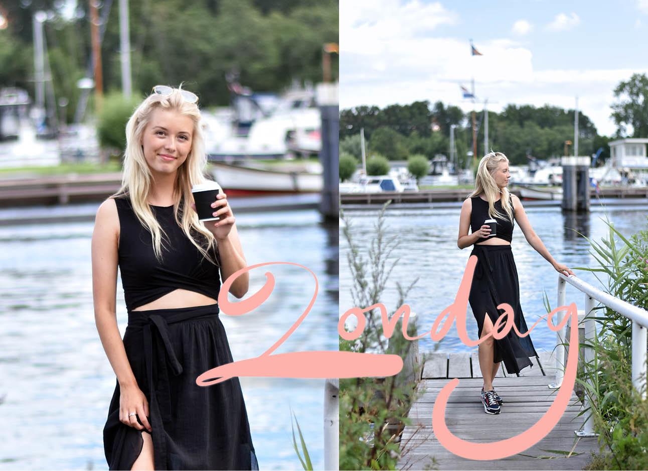 annabelle van hardeveld in de look of the day met een zwart cut our jurk, koffie op een steiger met water op de achtergrond
