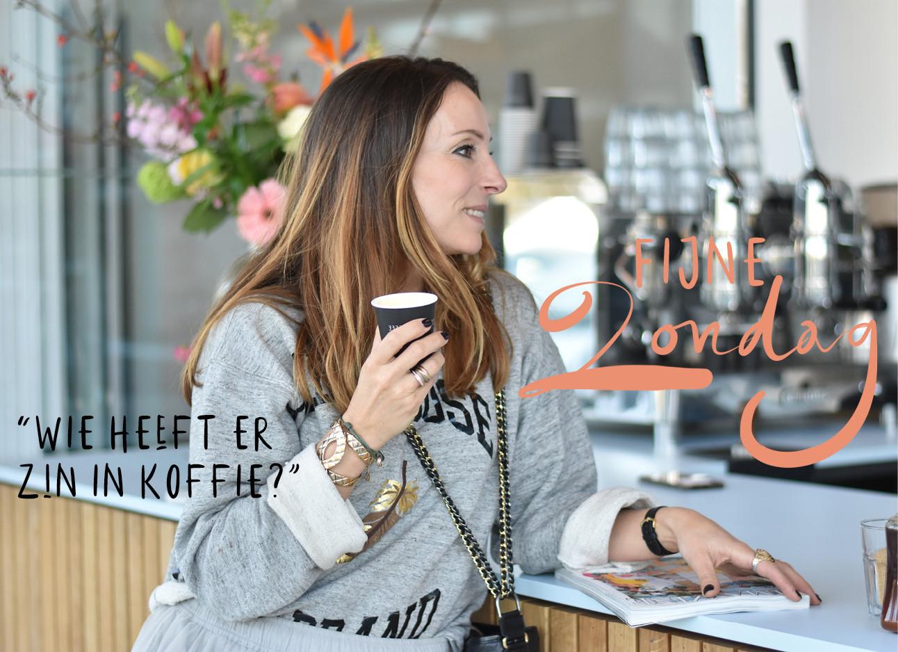may-britt mobach staat aan de bar van een koffietentje met een cappuccino in haar hand. ze draagt een grijze trui en op de bar ligt het runway report magazine van amayzine