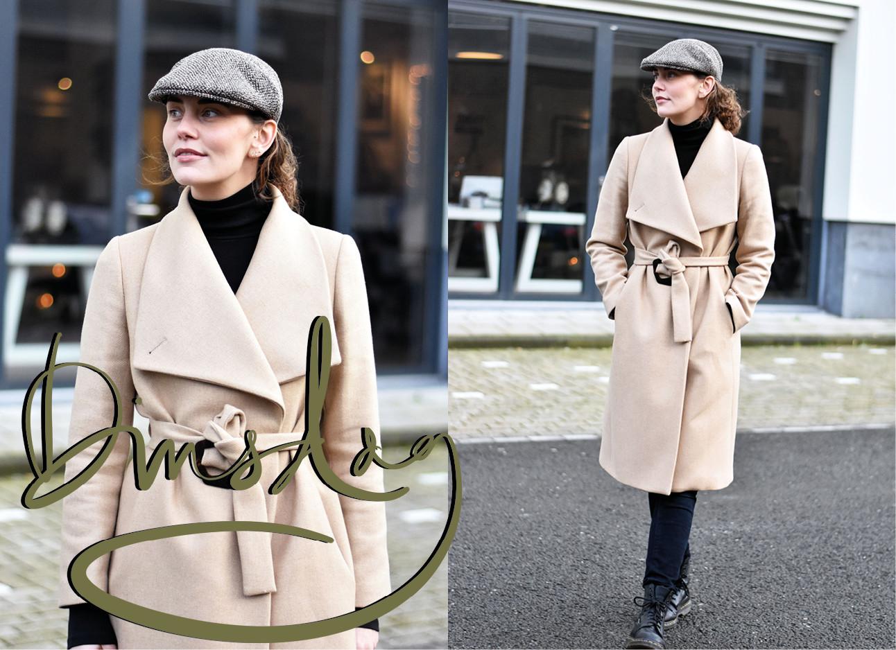 lianne die lachend buiten staat in een beige jas