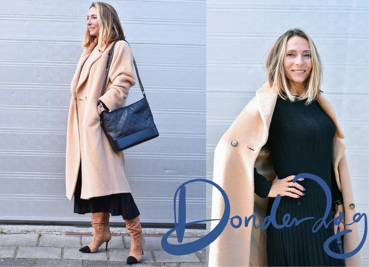 May die een licht bruine jas draagt met daaronder een blauw jurk met bruine laarsjes, ze staan voor een lichtblauwe muur
