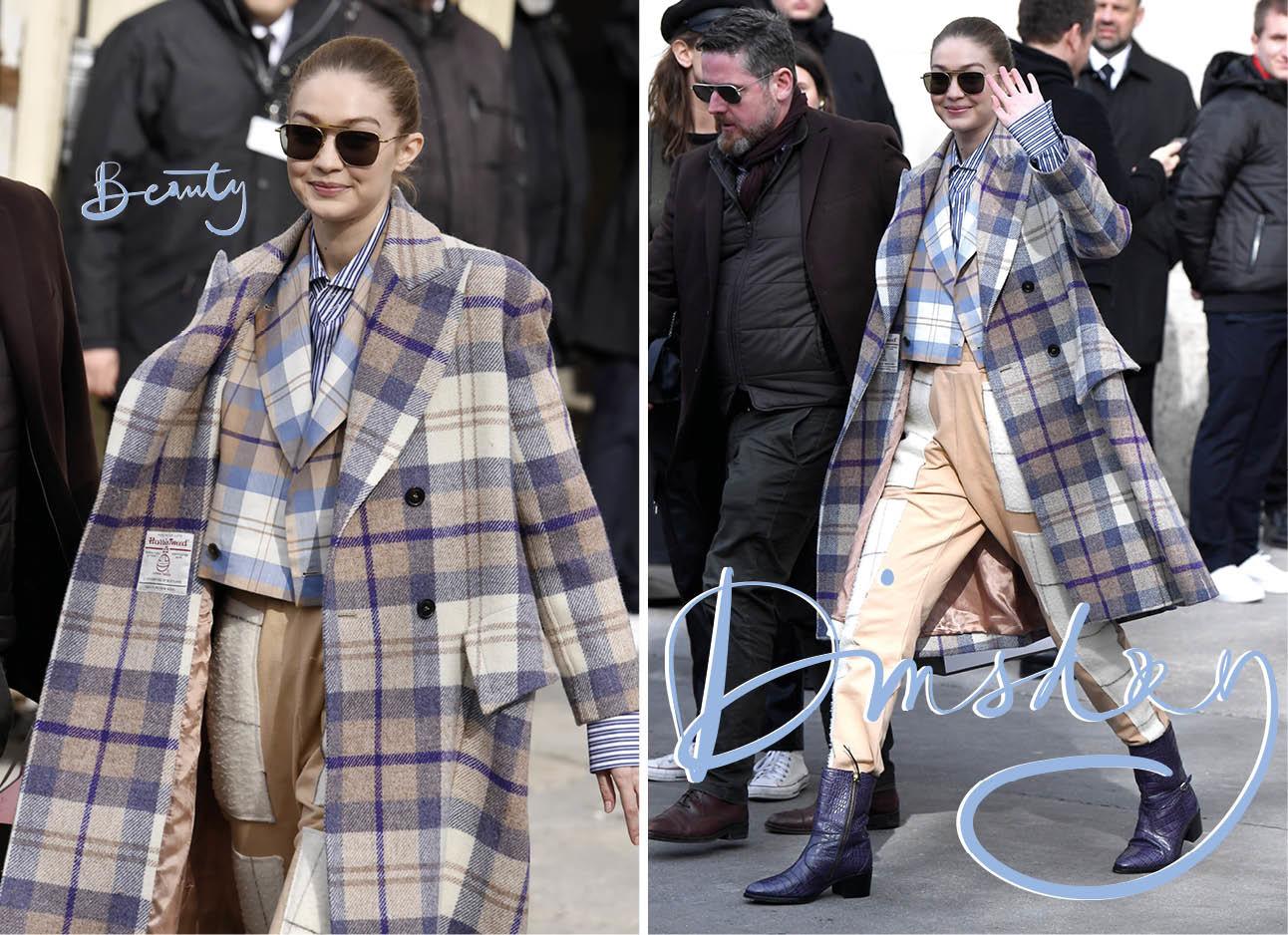 Gigi Hadid lopend over straat met een geruit jas aan en grote zonnebril op