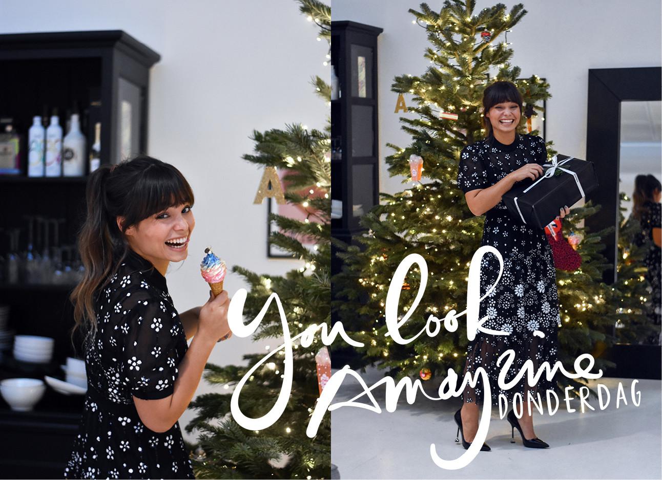 kiki die lachend voor de kerstboom staat