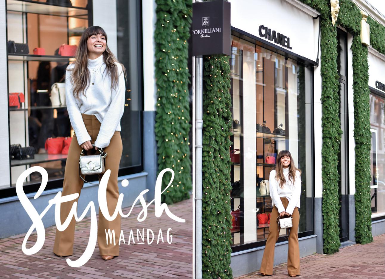 Kiki die in witte trui lachend voor de chanel winkel staat