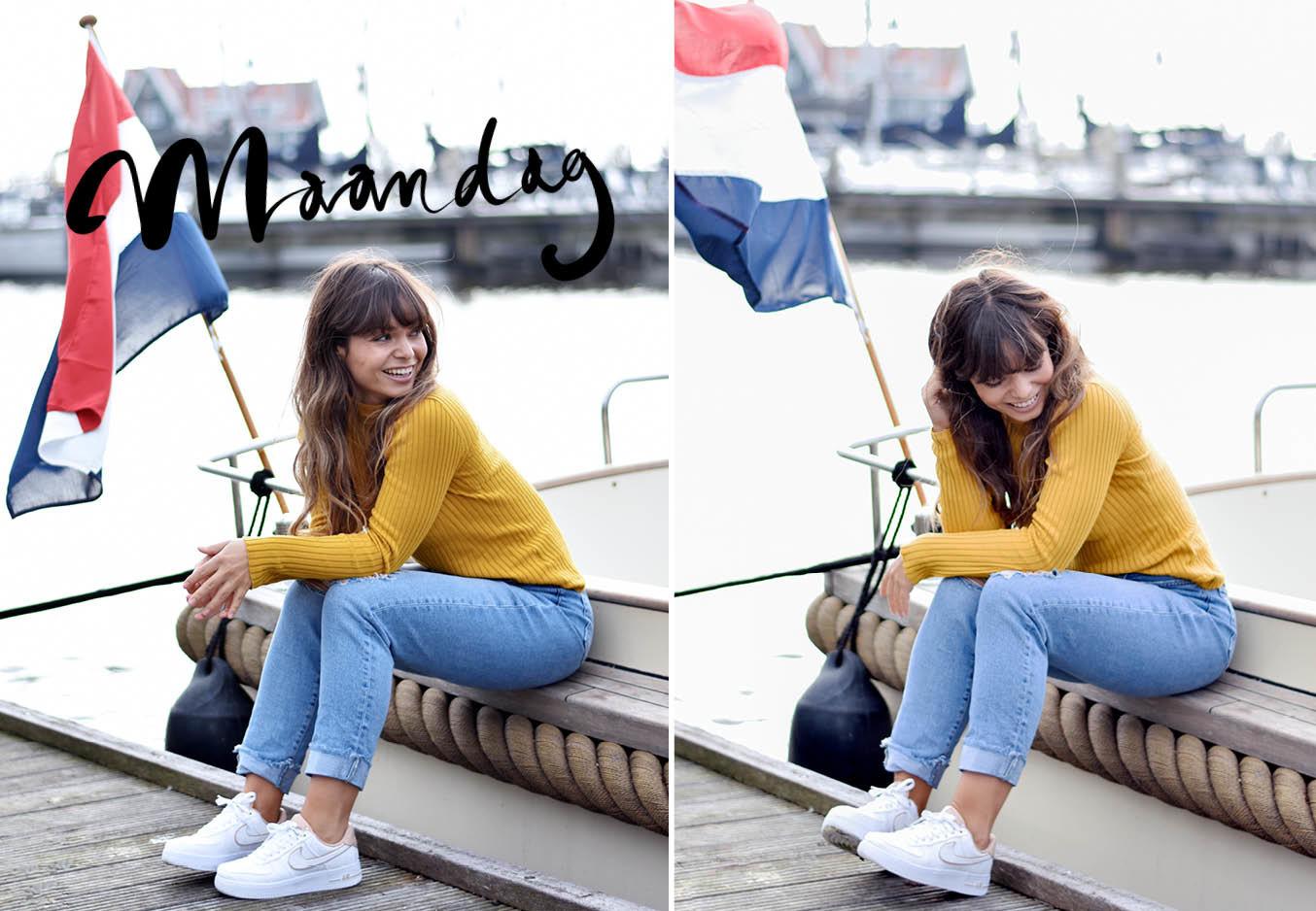 kiki duren lachend bij het water een een gele trui met jeans