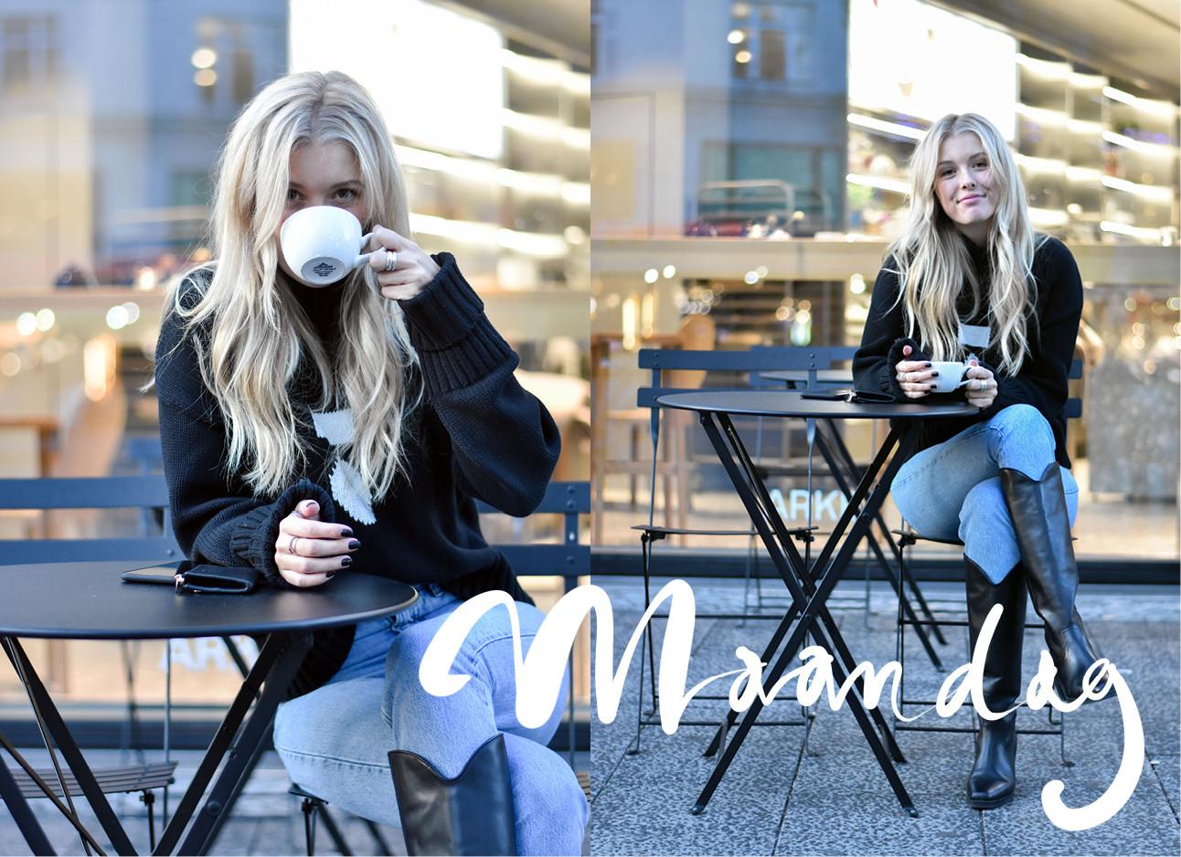 annabelle die op een zwarte stoel buiten zit met een bak koffie